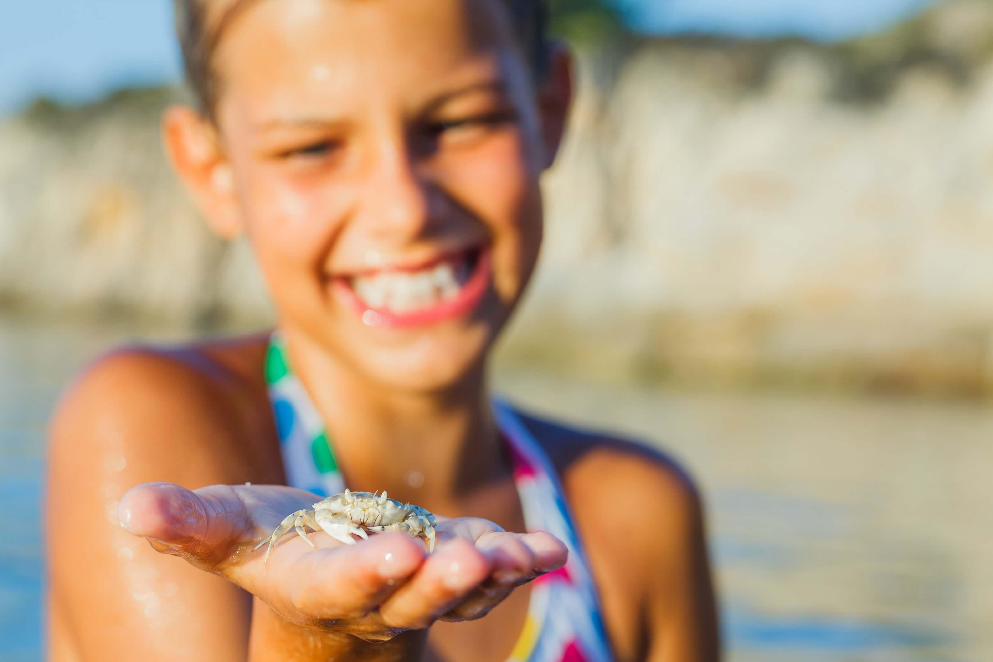 Meisje met krab op het strand