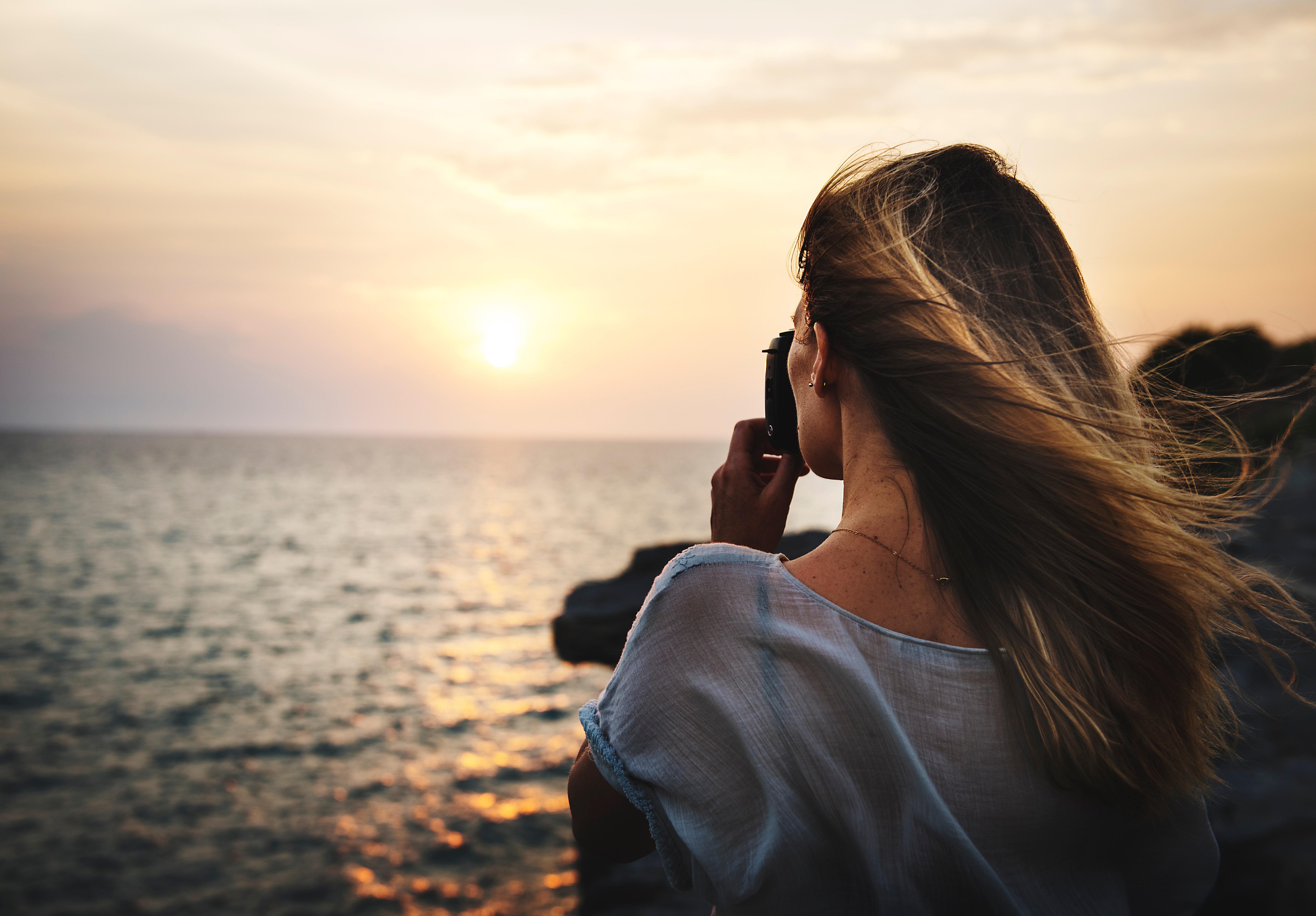 Vrouw maakt foto bij de zee